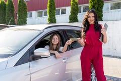 «samochodu czynszu «transakcja między dwa pięknymi kobietami zdjęcie stock