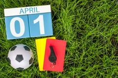 1º de abril dia 1 do mês, calendário no fundo da grama verde do futebol com equipamento do futebol Tempo de mola, espaço vazio pa Fotografia de Stock