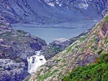 Is- ¼fisee och vattenfall för sjö HÃ i början av den alpina dalen av Maderanertal arkivfoto