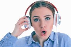 ¿La música que escucha de la mujer con los auriculares de un teléfono elegante y pregunta lo que? Foto de archivo libre de regalías