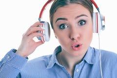 ¿La música que escucha de la mujer con los auriculares de un teléfono elegante y pregunta lo que? Fotografía de archivo libre de regalías