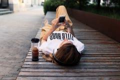 ¿Música que escucha femenina adolescente al aire libre, mintiendo en banco y relajándose? verano Fotos de archivo
