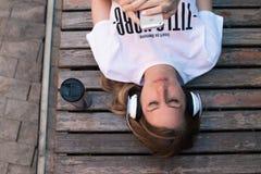 ¿Música que escucha femenina adolescente al aire libre, mintiendo en banco y relajándose? verano Imagenes de archivo
