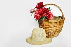 ¿peonías de la Ð-tinta? sombrero en una cesta de mimbre fotos de archivo