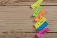 ¿Preguntas por qué? ¿Qué? ¿Dónde? ¿Cuándo? ¿Por qué? ¿Cómo? en etiquetas engomadas coloridas en el escritorio de madera foto de archivo libre de regalías