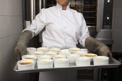 ¿Sacando del horno una bandeja de Cr? caramelos de los mes Imagen de archivo