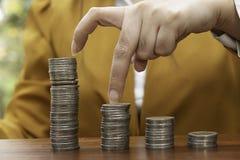 ีBusiness kobiety używają palcowe tempo monety na stercie monety używają dla pieniądze bankowość pieniężnego pojęcia obrazy stock