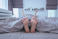 ฺฺBarefoot, pés e estiramento preguiçosamente na cama após acordar fotografia de stock royalty free