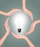 ิีิbulb light is surrounded by hands. Bulb light in woman hand on green background royalty free stock images