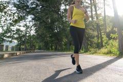 ํYoung fitness sports woman runner running on tropical park trail, Young fitness woman running at morning tropical forest trail stock image
