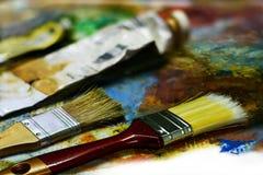 ์New and old paint brushes with old color tubes on the palette Royalty Free Stock Image