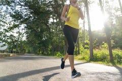à ¹  à ¹  junger Eignungssport-Frauenläufer, der auf tropischer Parkspur, junge Eignungsfrau läuft am tropischen Wald des Morge stockfotografie
