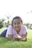 à ¹ Mädchen lag auf Feld des grünen Grases mit nettem Gefühl stockfotos