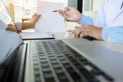 ชTwo врачует обсуждать терпеливые примечания в офисе указывая к a Стоковые Фотографии RF