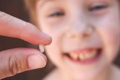 À 6 années l'enfant a perdu la dent de lait La fille tient la dent dans sa main Photographie stock