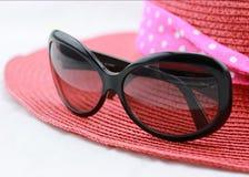 ฺBlacksolglasögon och röd hatt Royaltyfri Bild