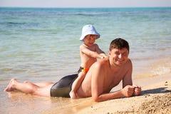 à califourchon sur le fils s'asseyant de père Images libres de droits