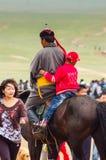À cheval garçon et homme sur la steppe, course de cheval de Nadaam Photographie stock