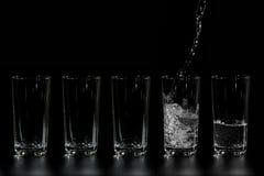 À cinq verres de l'eau propre est versée Photos stock