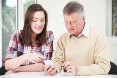 À grand-père adolescent de petite-fille montrant comment employer le phone mobile Photo libre de droits