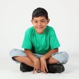 À jambes en travers se reposant de sourire du garçon d'école 9 sur l'étage Photo libre de droits