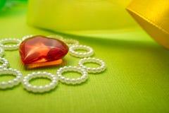 À l'humeur pour l'amour pour le cadeau et la déclaration de l'amour, au coeur rouge du verre et à un arrière-plan vert luxuriant Images libres de droits