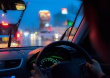 À l'intérieur d'une voiture conduite par une femme sous la pluie par nuit Photographie stock libre de droits