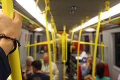 À l'intérieur de la voiture de souterrain avec la main du banlieusard Photographie stock libre de droits