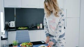 À la cuisine la fille dans des pyjamas prépare la salade du brocoli et du poivron doux, repas sain clips vidéos