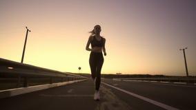 À la fille de sport de coucher du soleil courant sur la route Beau ciel banque de vidéos