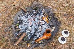 À la forêt d'enjeu au printemps, un pot de café turc d'argile est chauffé contre l'herbe photo stock