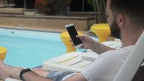 À la piscine l'homme tient un téléphone avec l'Internet à un hôtel de luxe banque de vidéos