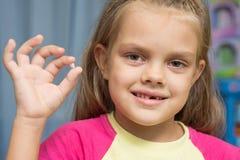 À la vieille fille de cinq ans est tombée la dent de lait d'avant supérieur Photos libres de droits