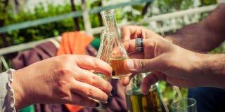 À la votre ! Main grillant avec des verres d'eau-de-vie fine Photographie stock libre de droits