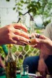 À la votre ! Main grillant avec des verres d'eau-de-vie fine Image stock