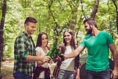 À la votre ! Quatre amis heureux, faisant tinter leurs bouteilles de bière dans a Images libres de droits