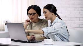 À mère moderne de fille enseignant comment employer encaisser des technologies en ligne et modernes photo stock