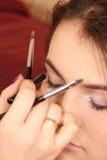 À moça compõe os olhos, põem cosméticos Foto de Stock