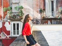 À moda, jovem mulher no fundo de casas coloridas imagens de stock royalty free