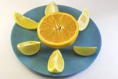 À moitié orange avec des tranches de citron de plat bleu Photographie stock