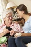 À petite-fille de grand-mère montrant comment faire du crochet à la maison photos libres de droits