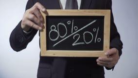 80 à 20 pour cent écrits sur le tableau noir, homme tenant le signe, principe de Pareto clips vidéos