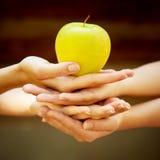 À quatre mains avec la pomme image libre de droits