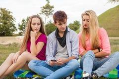 À qui est-il écrivant ? Trois amis en parc ensoleillé Photo stock