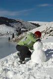 À un bonhomme de neige de construction Images stock