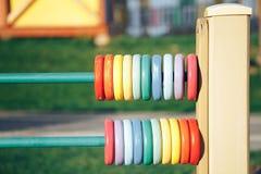 Ábaco de madeira da cor Círculos de madeira coloridos no campo de jogos imagem de stock