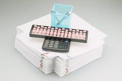 Ábaco e calculadora com a caixa azul da pena colocada no documento Foto de Stock Royalty Free