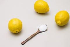 Ácido cítrico en cuchara de madera y limones frescos fotos de archivo libres de regalías