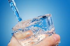 A água é derramada dentro um vidro Imagens de Stock Royalty Free