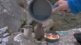 A água é derramada em um potenciômetro do café Close-up Almoço no banco de um rio da montanha video estoque